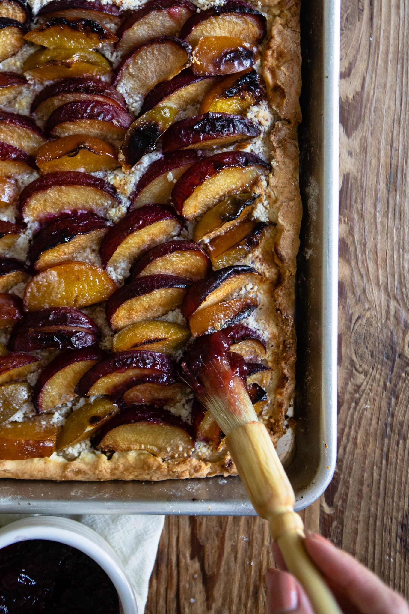 plum tart with raspberry jelly on a baking sheet against a wood backdrop