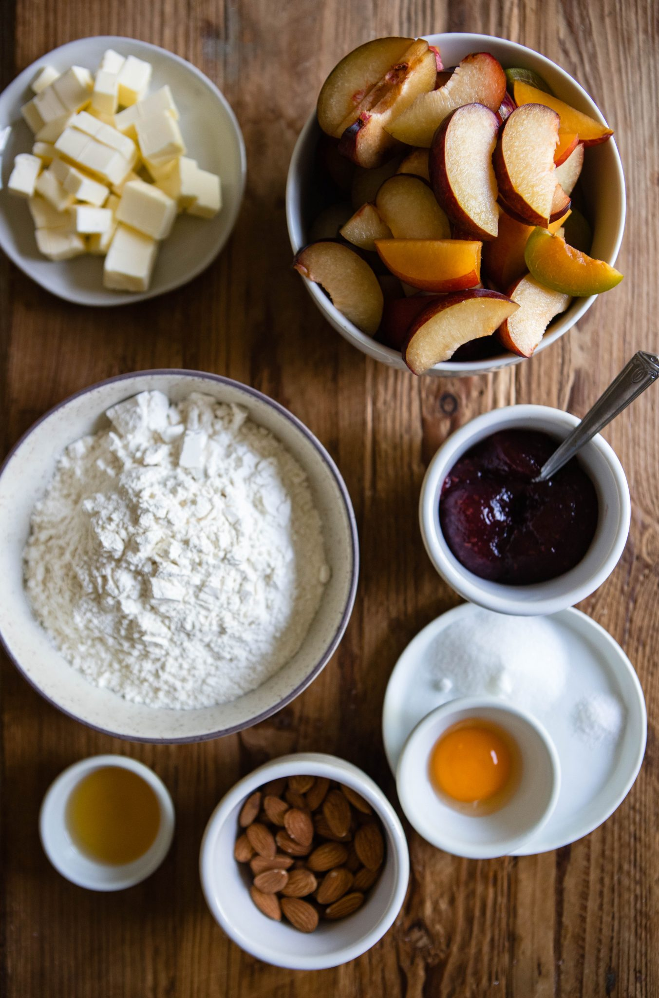 rustic plum tart ingredients on a wood surface
