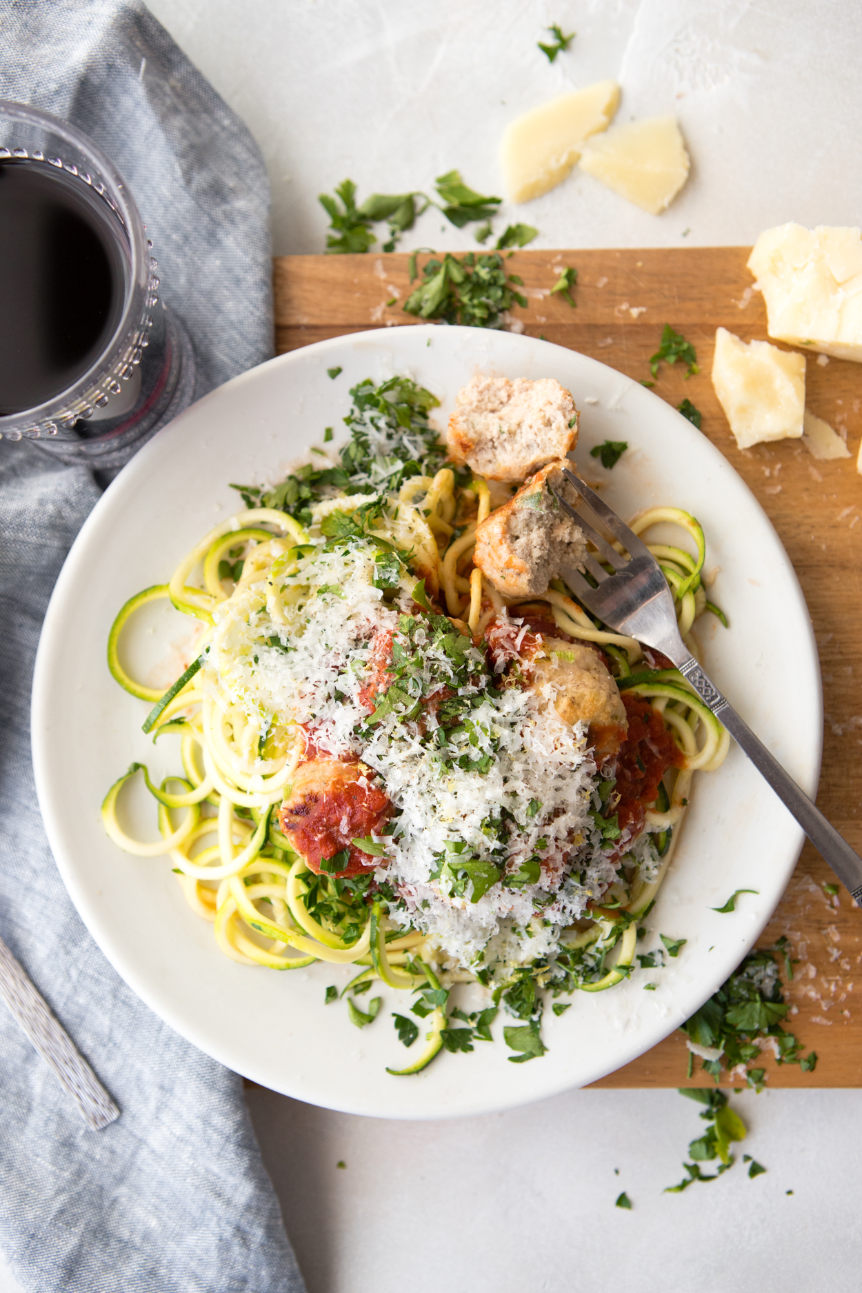 healthy turkey meatballs and zucchini noodles and marinara sauce on a white plate set on a wooden board with a glass of red wine