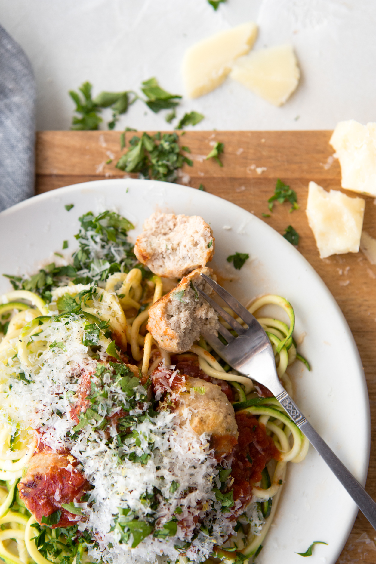 a fork digging into a plate of healthy turkey meatballs zucchini noodles and marinara sauce dished up on a white plate