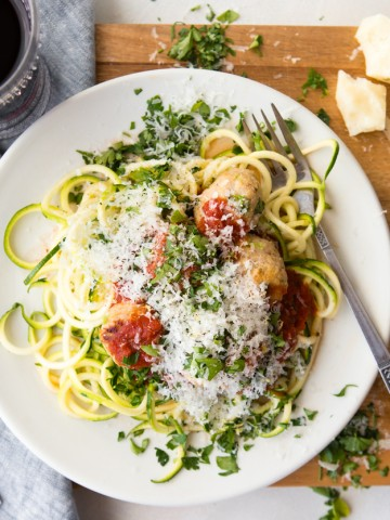 healthy turkey meatballs and zucchini noodles and marinara sauce on a white plate with a fork set on a wooden board with a glass of red wine
