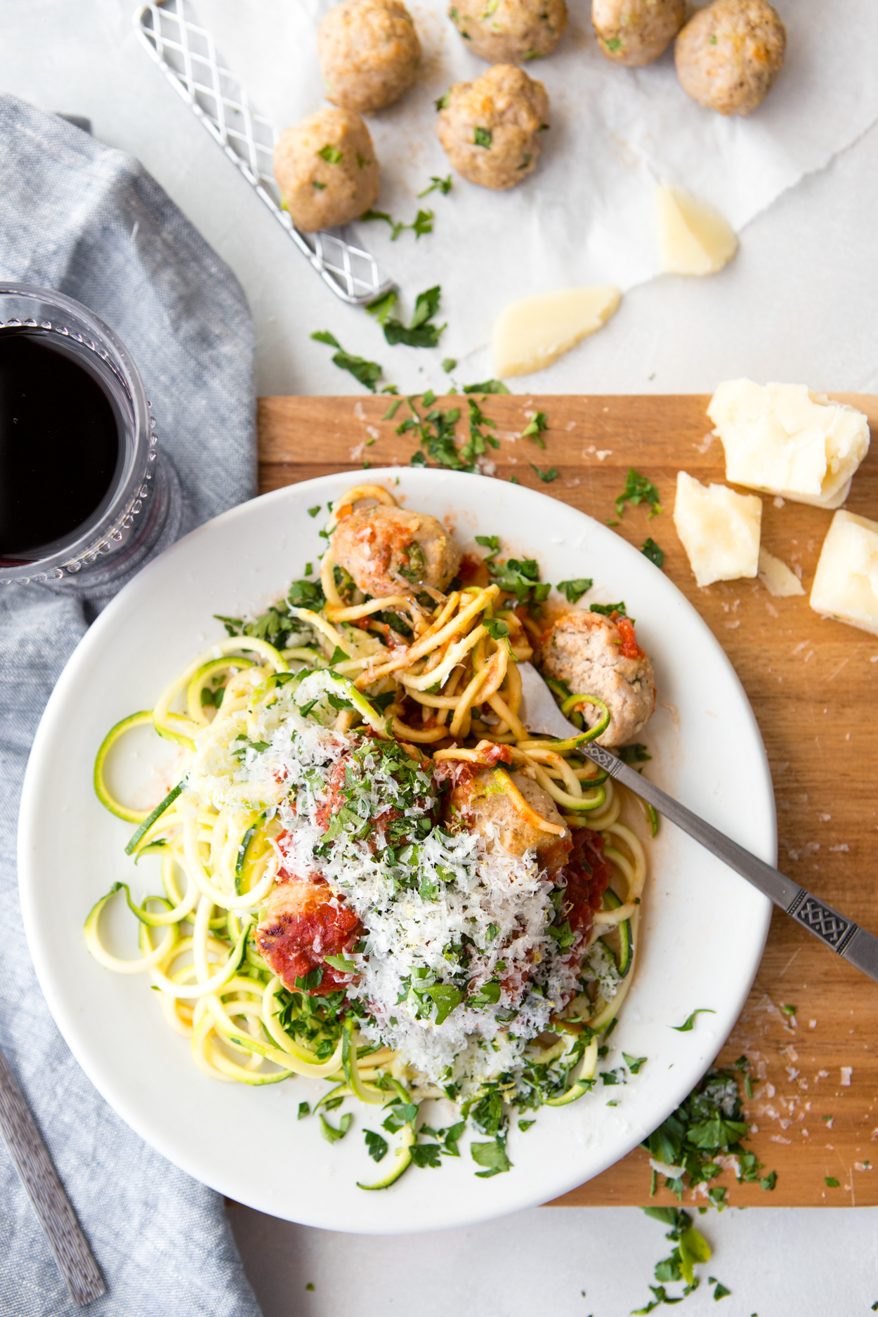 a tray of baked meatballs set next to a white round plate filled with zoodles, marinara sauce and healthy turkey meatballs
