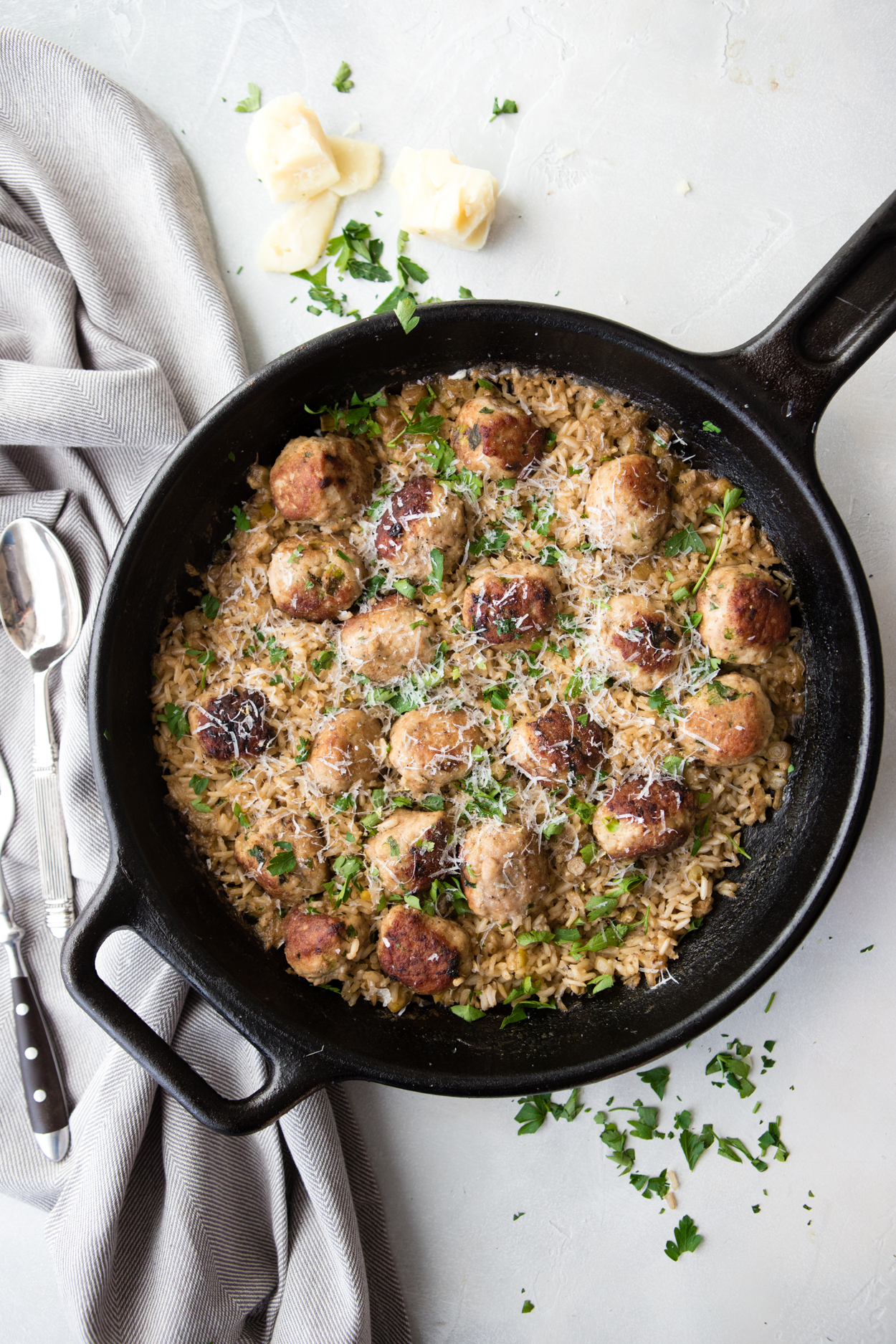 turkey meatballs and brown rice in a cast iron skillet on a white background