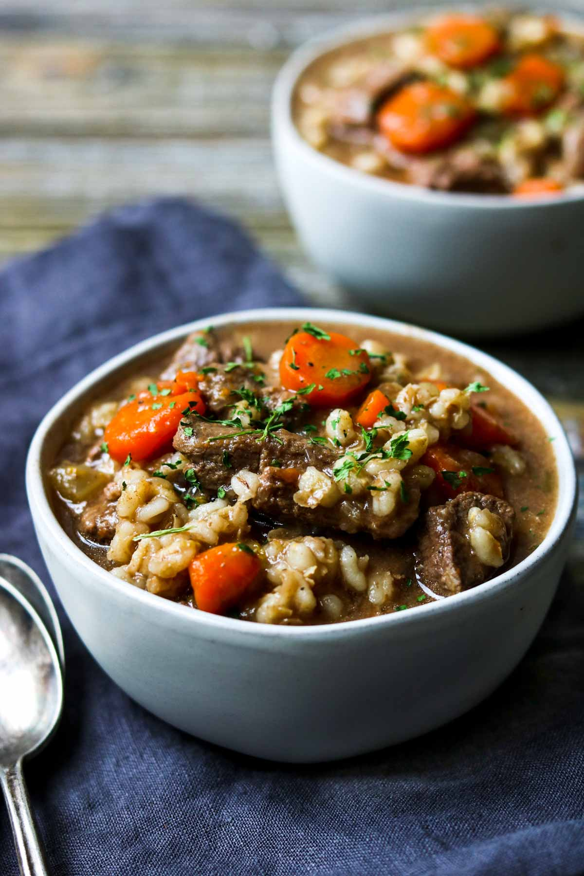 Instant Pot Beef and Barley Stew in a white bowl with a blue napkin