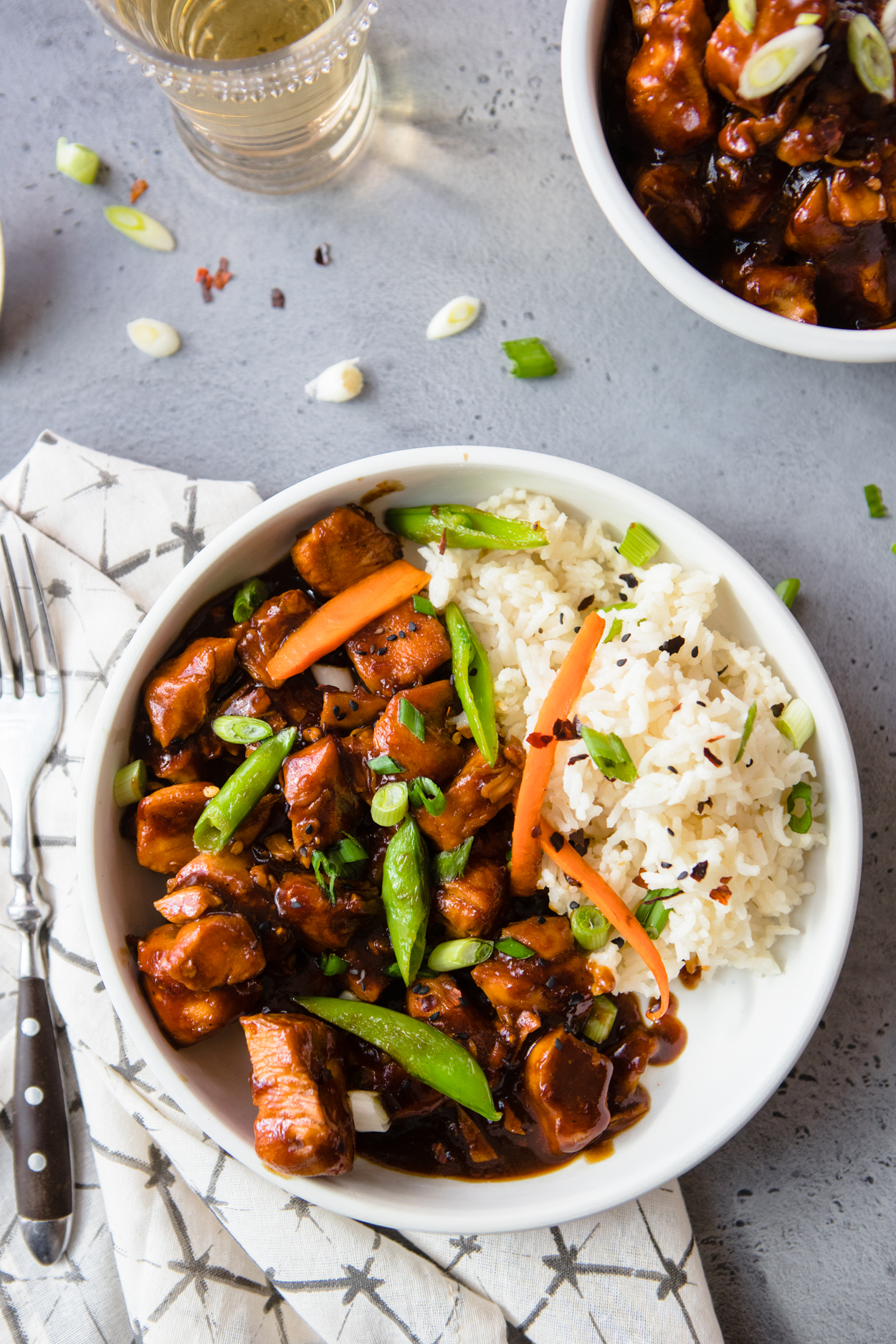 General Tso's Instant Pot Chicken with Rice in a white bowl sitting on a napking with a fork