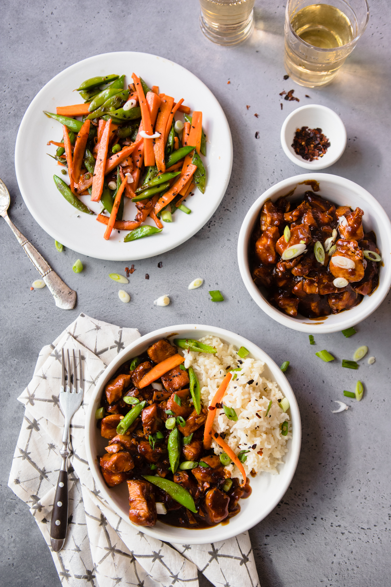 General Tso's Instant Pot Chicken in a white bowl with a side of carrots and snow peas, and a bowl of General Tso's Chicken and rice