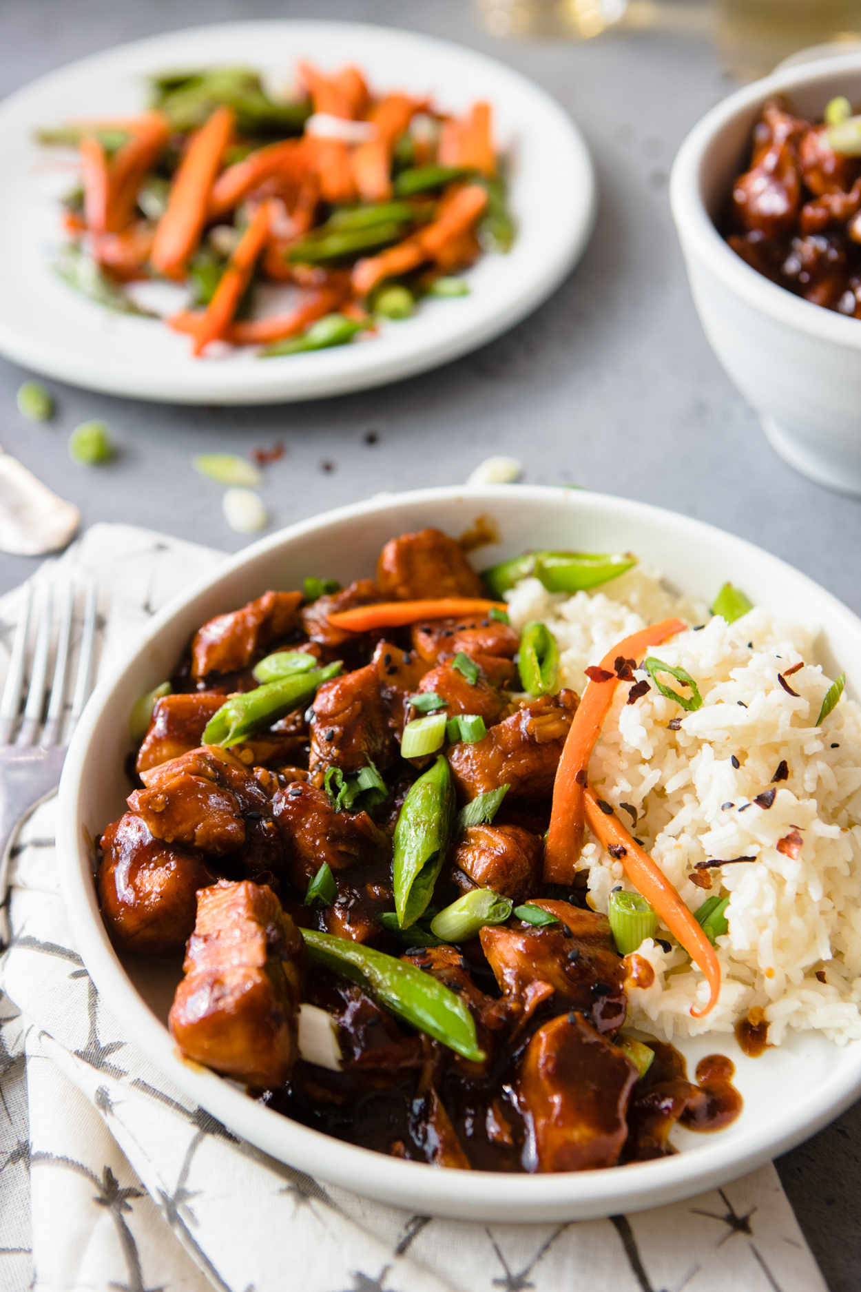 A white bowl full of General Tso's Chicken and rice garnished with scallions and carrots