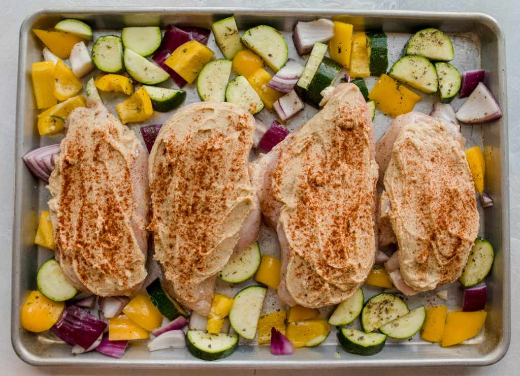 cut up vegetables and chicken with hummus on a baking sheet