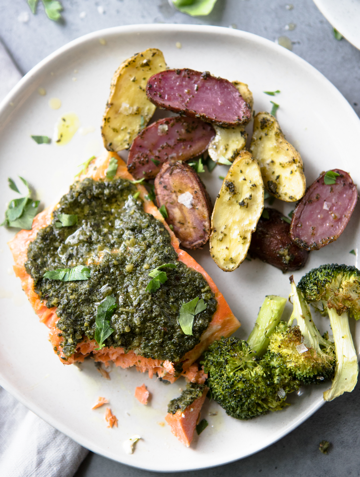 baked salmon with pesto, potatoes and broccoli on a white round plate
