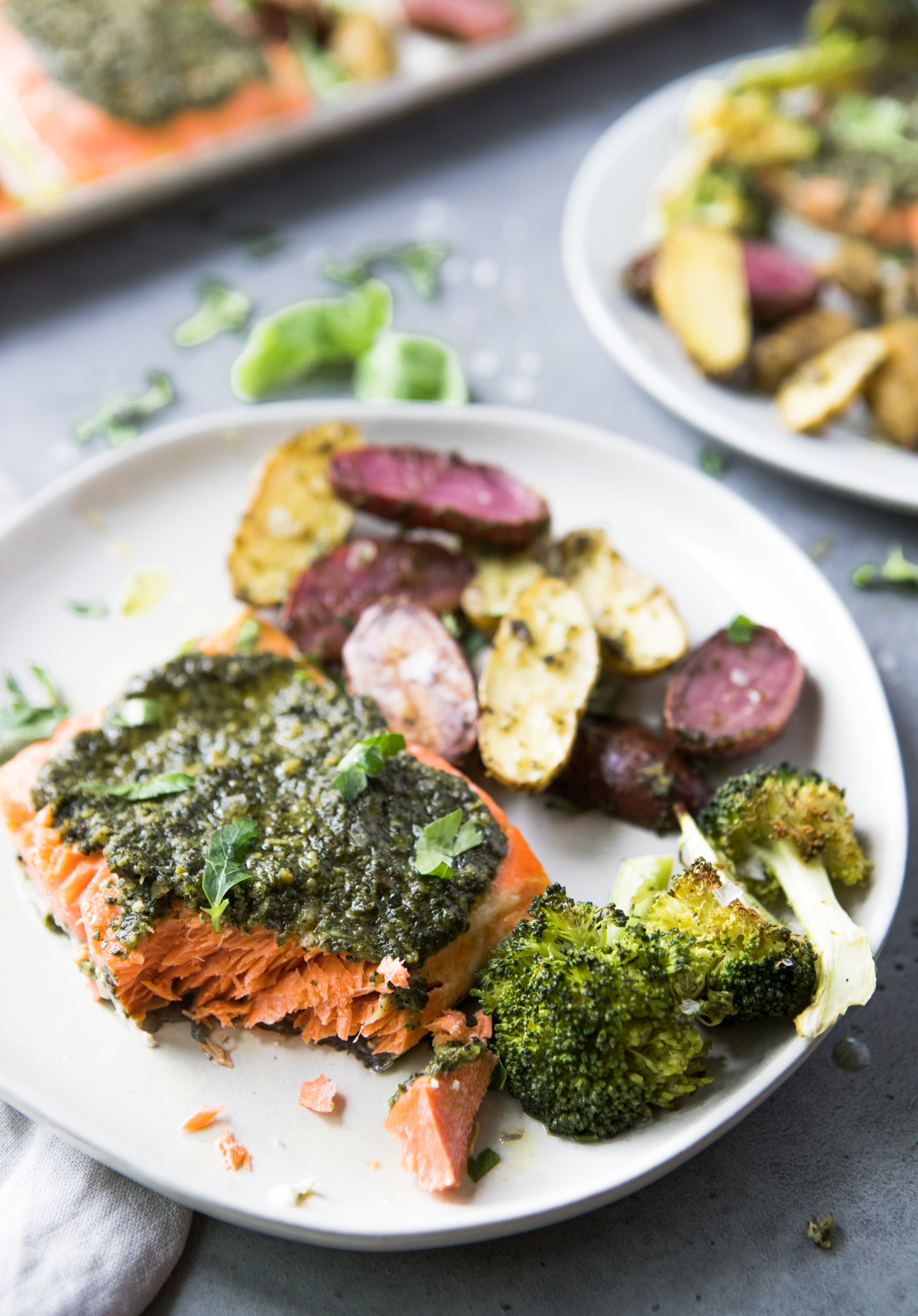 Baked salmon with pesto and broccoli and potatoes on a white round plate