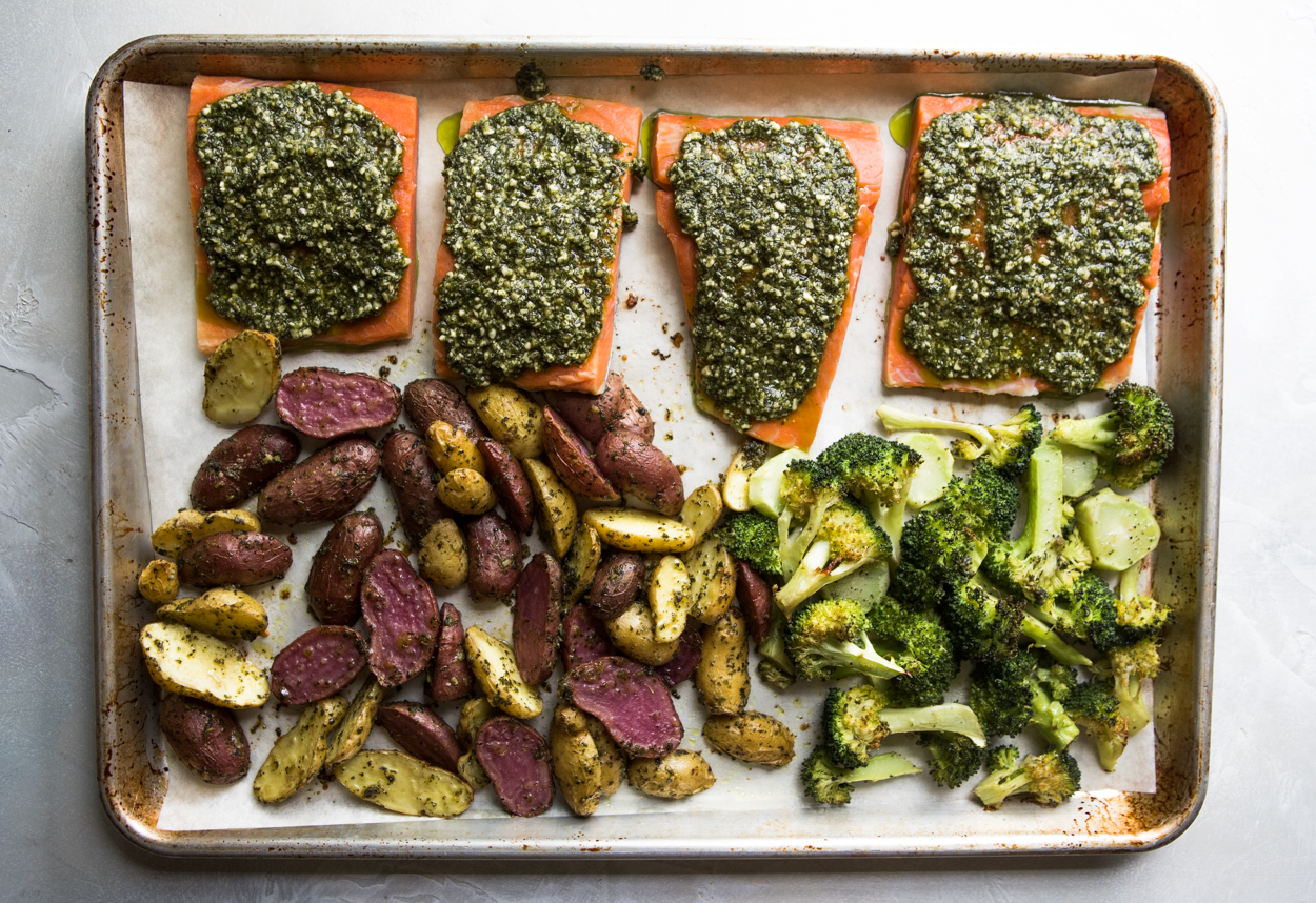 broccoli, potatoes, salmon and pesto on a baking sheet