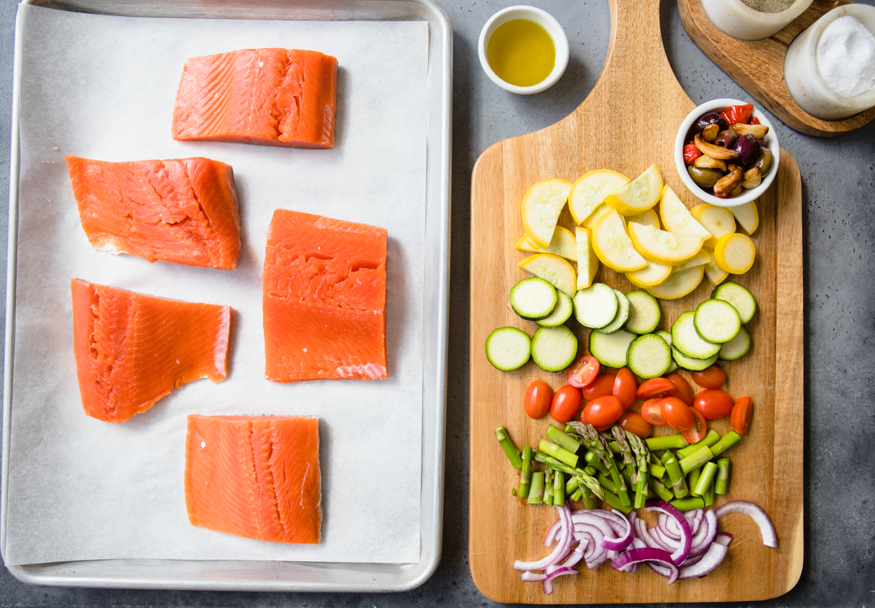 Sheet pan with parchement paper and salmon, veggies on a cutting board to the side