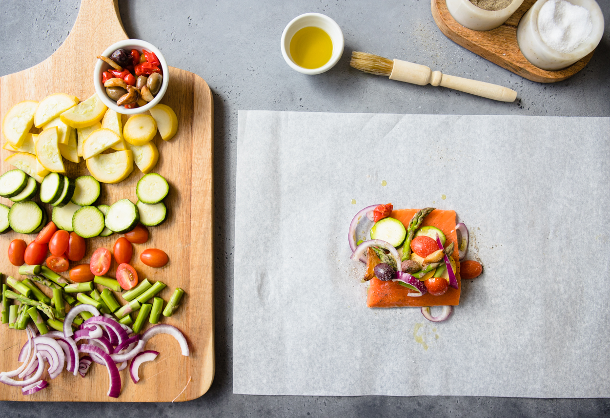 A piece of salmon topped with veggies on a sheet of parchment paper