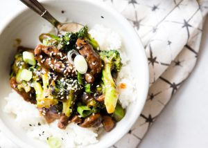 Instant Pot beef and broccoli in a white bowl over rice