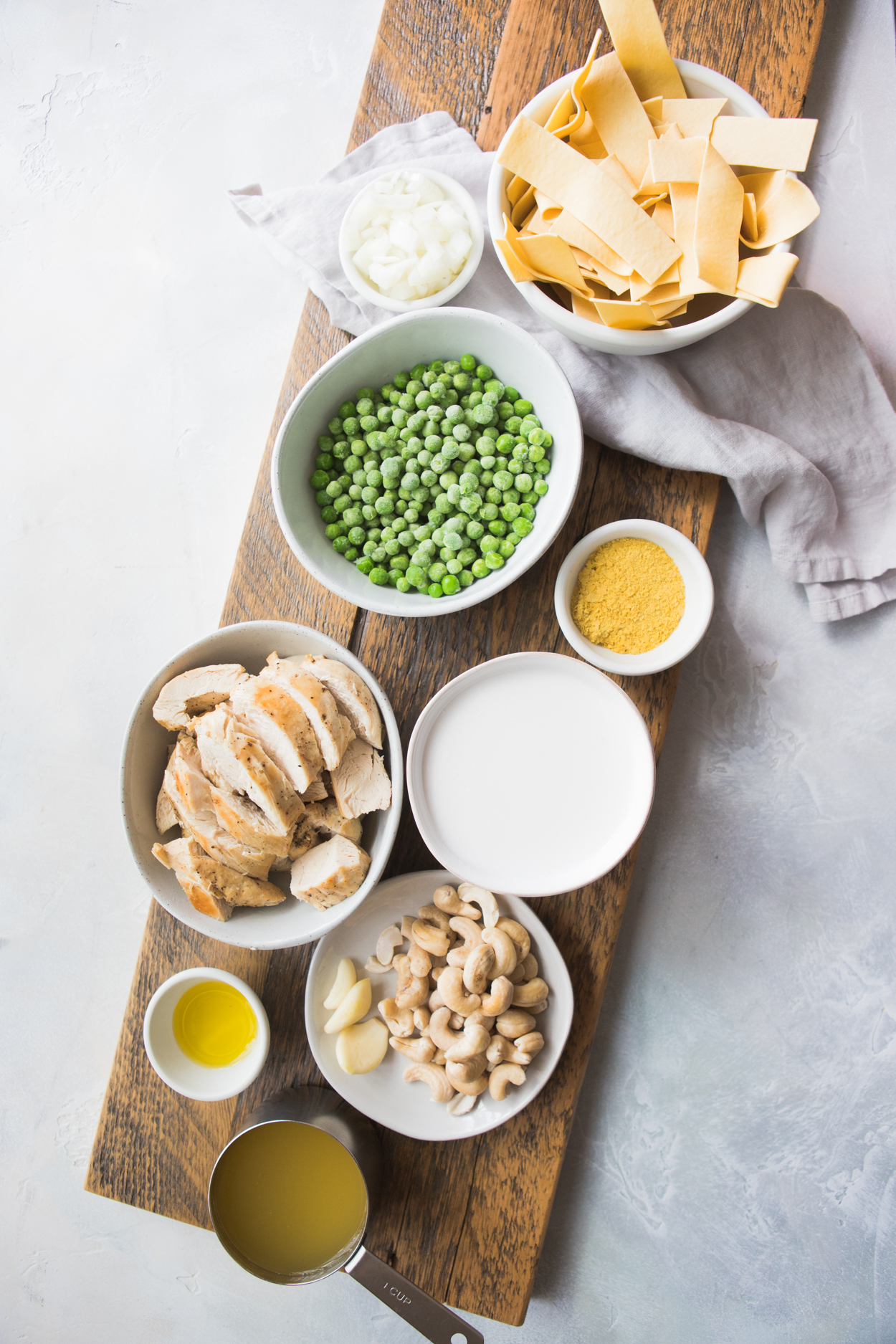 Instant Pot Chicken Alfredo ingredients in white bowls- chicken, cashews, pasta, peas, nutritional yeast, onions, oil, lemon juice and chicken broth