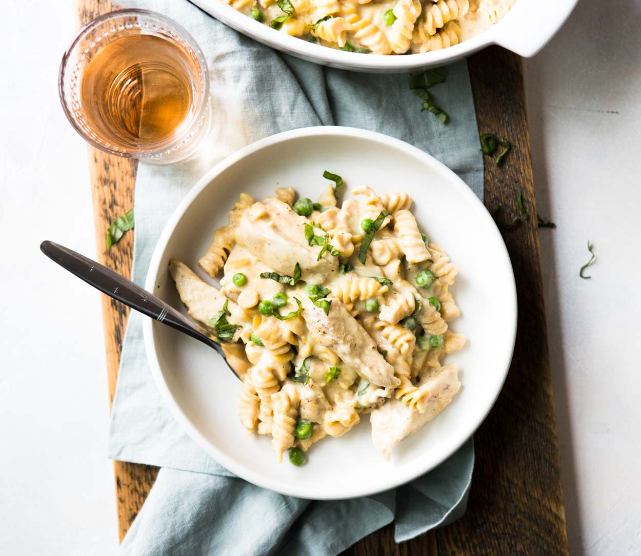 Instant Pot Chicken Pasta in a white dish with a dairy free alfredo sauce peas and basil