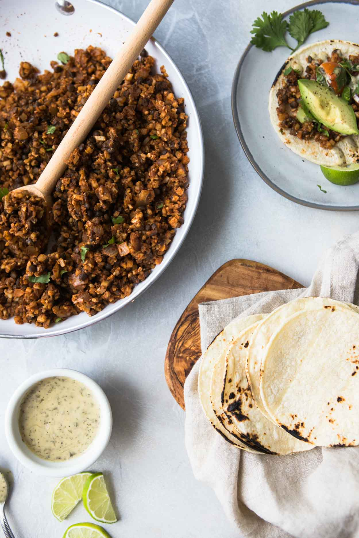 Cauliflower rice and lentil tacos in a white pan against a white board