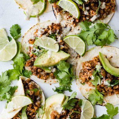 Cauliflower rice tacos on flour tortillas with cilantro, avocado and limes