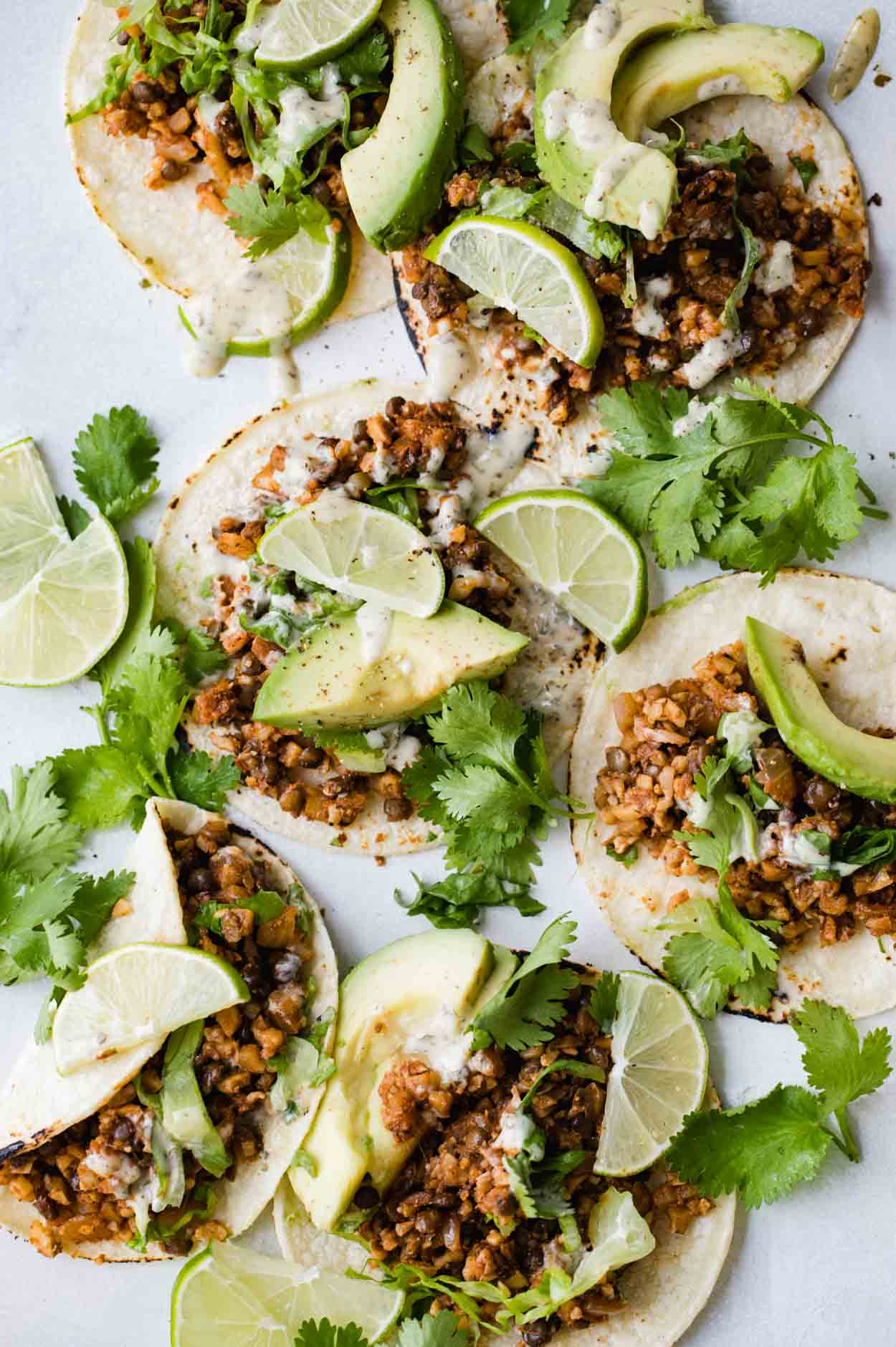 Cauliflower rice and lentil tacos on corn tortillas with limes, avocado and cilantro on a white board
