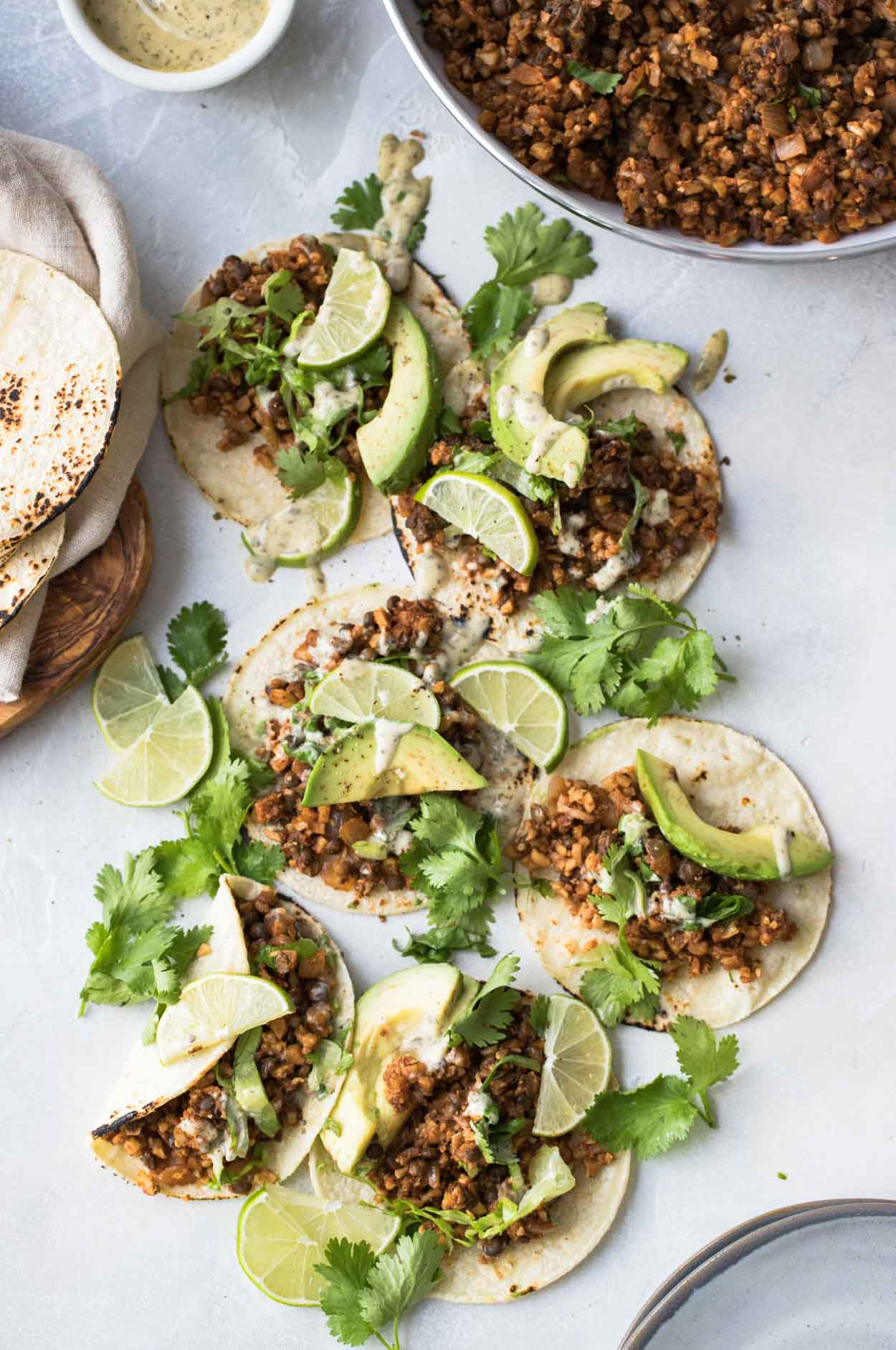 Cauliflower rice and lentil tacos on corn tortillas with limes, cilantro and avocado on a white board