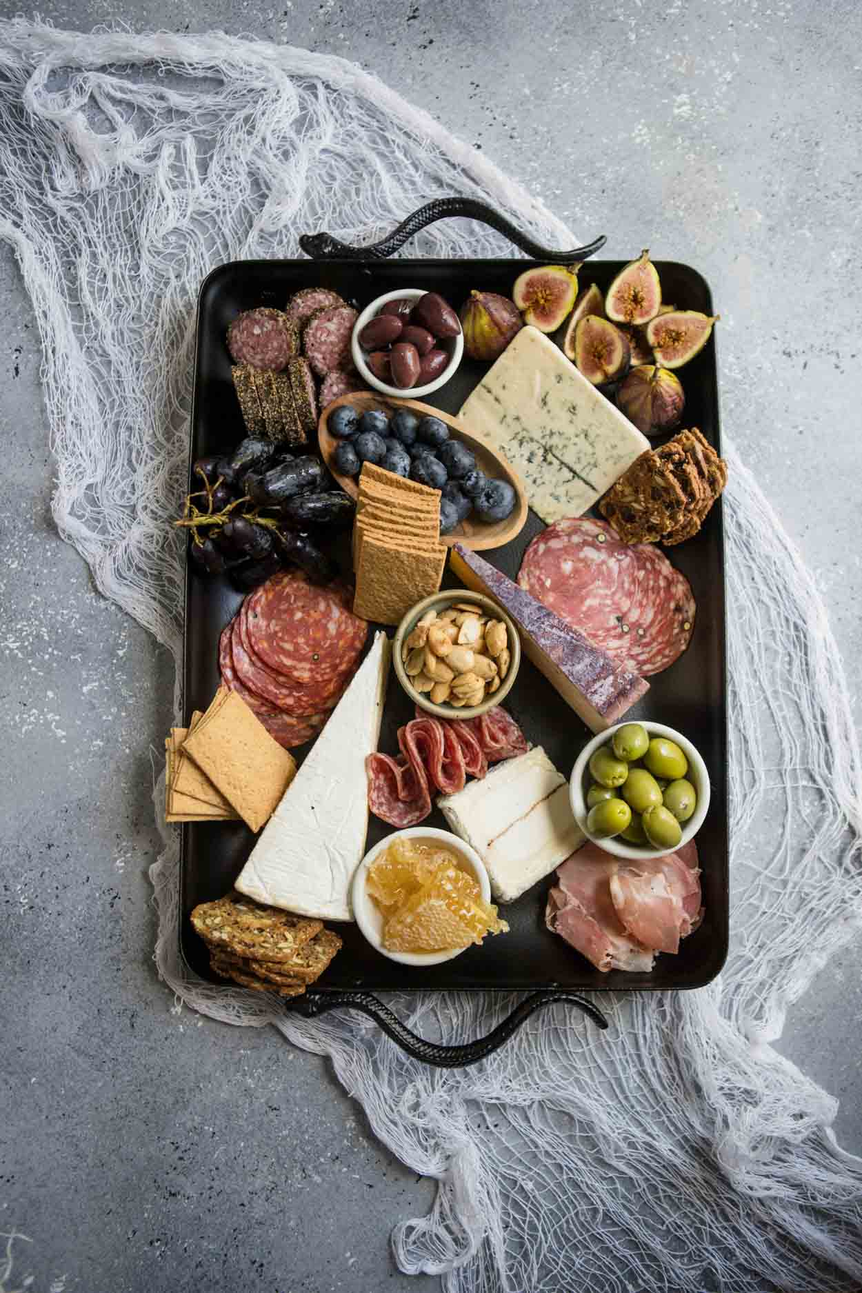 Charcuterie board on a black platter with spiders and skeleton hand on a gray board