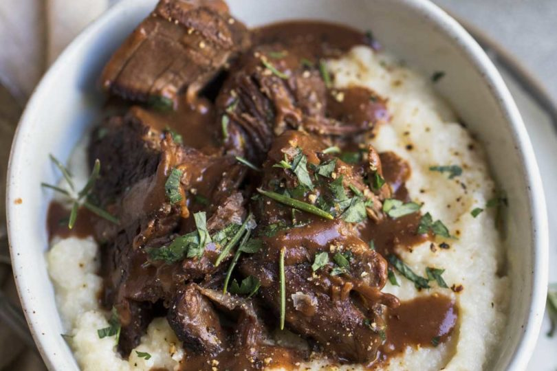 Pot roast and mashed cauliflower with gravy and herbs in a white bowl
