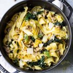 Wide egg noodles with sausage, kale and fennel in a black cast iron pot on a gray surface