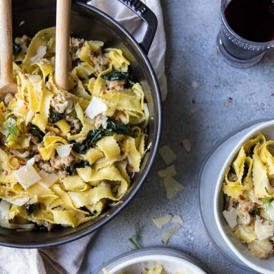 Wide egg noodles with sausage, kale and fennel in a black cast iron pot and on 2 gray bowls on a gray surface