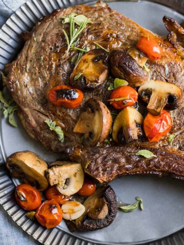 Steak, mushrooms, tomatoes and herbs on a tin plate with a bowl of mushrooms and tomatoes next to it and sliced meat on a cutting board, on top of a white background