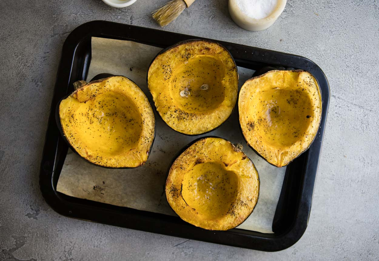 Roasted acorn squash on a black baking sheet on a gray surface