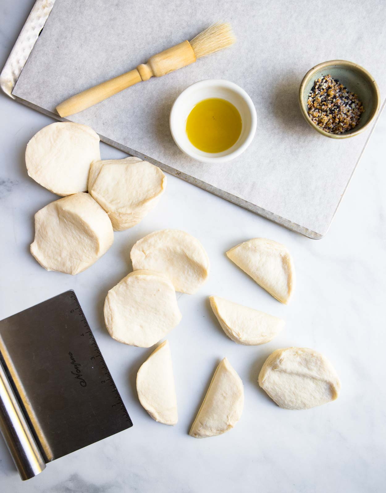 biscuit dough and olive oil and pastry cutter on marble surface