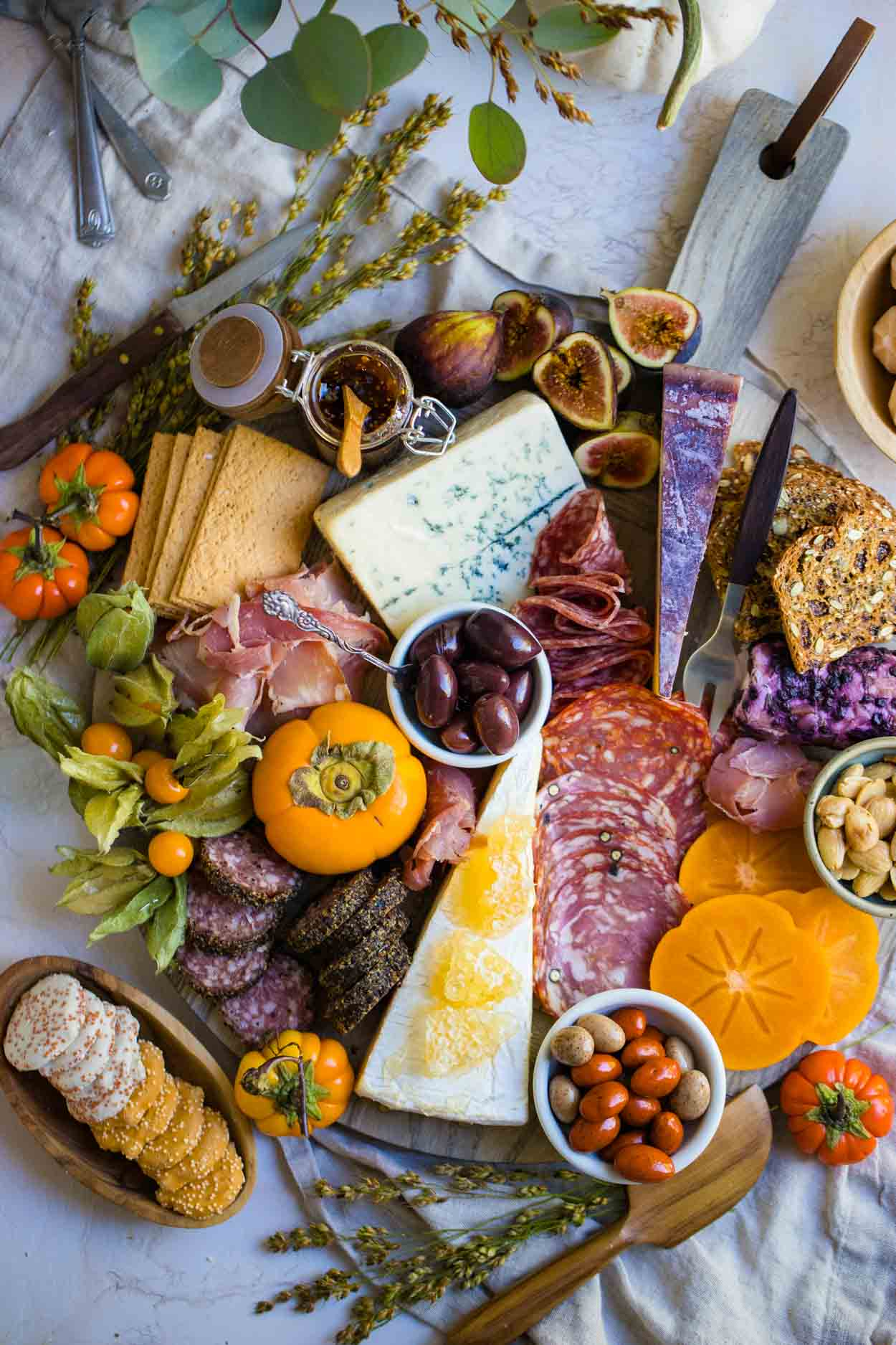 a charcuterie board with meats, cheese, and other foods