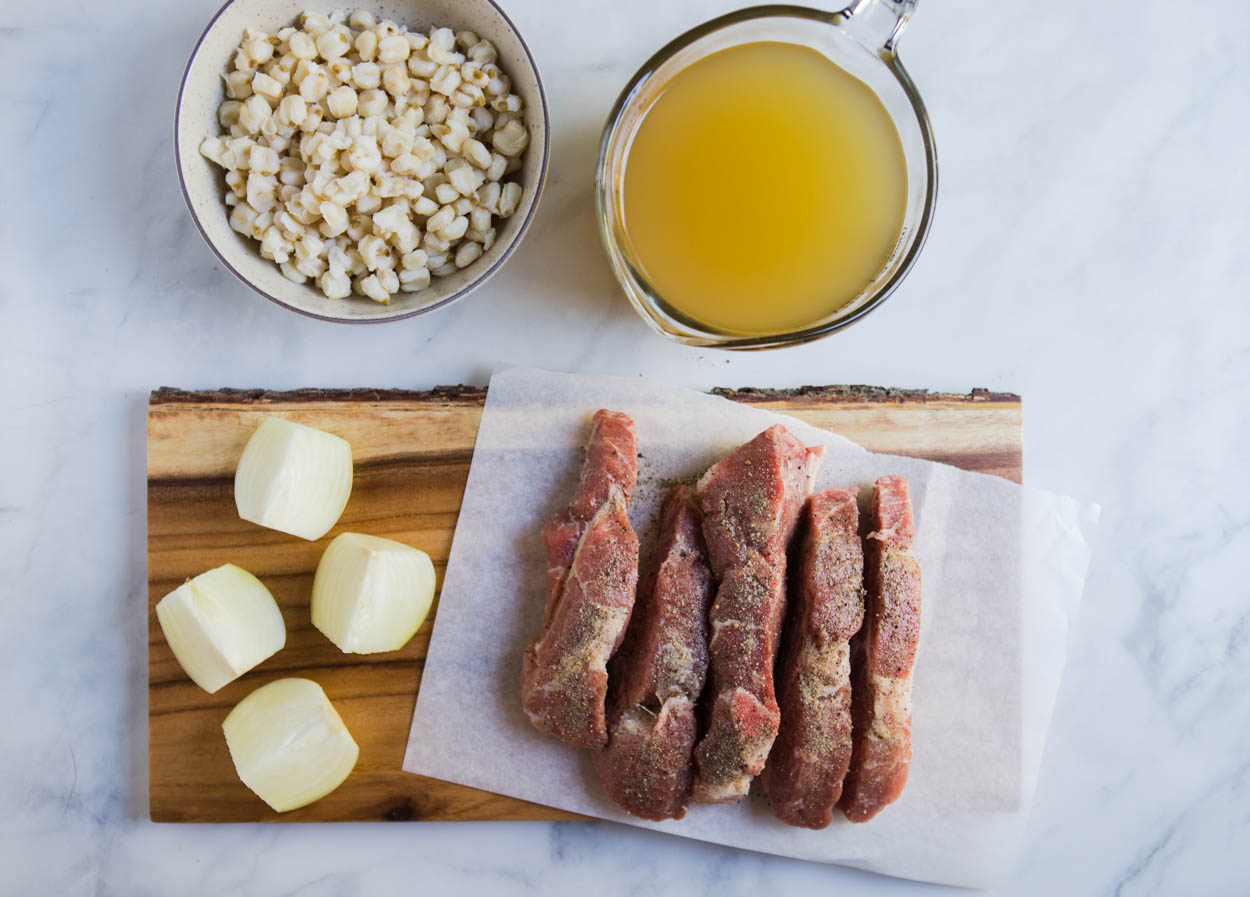 pieces of country style pork ribs set on a piece of parchment paper, alongside cut up onion, a bowl of hominy, and chicken broth