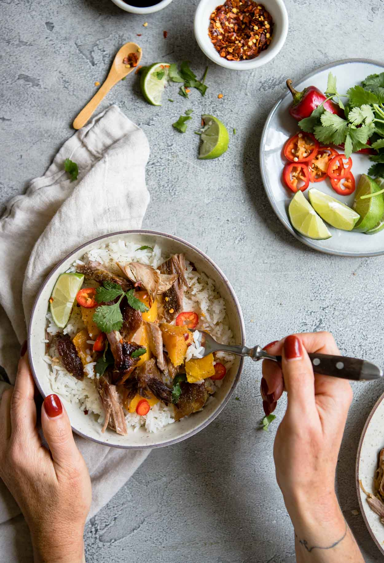 woman's hand holding a round bowl filled with rice and braised Asian pork and topped with garnishes