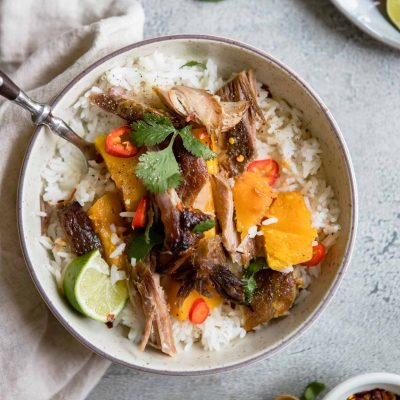 round bowl filled with rice, and topped with butternut squash, braised Asian pork shoulder and garnishes
