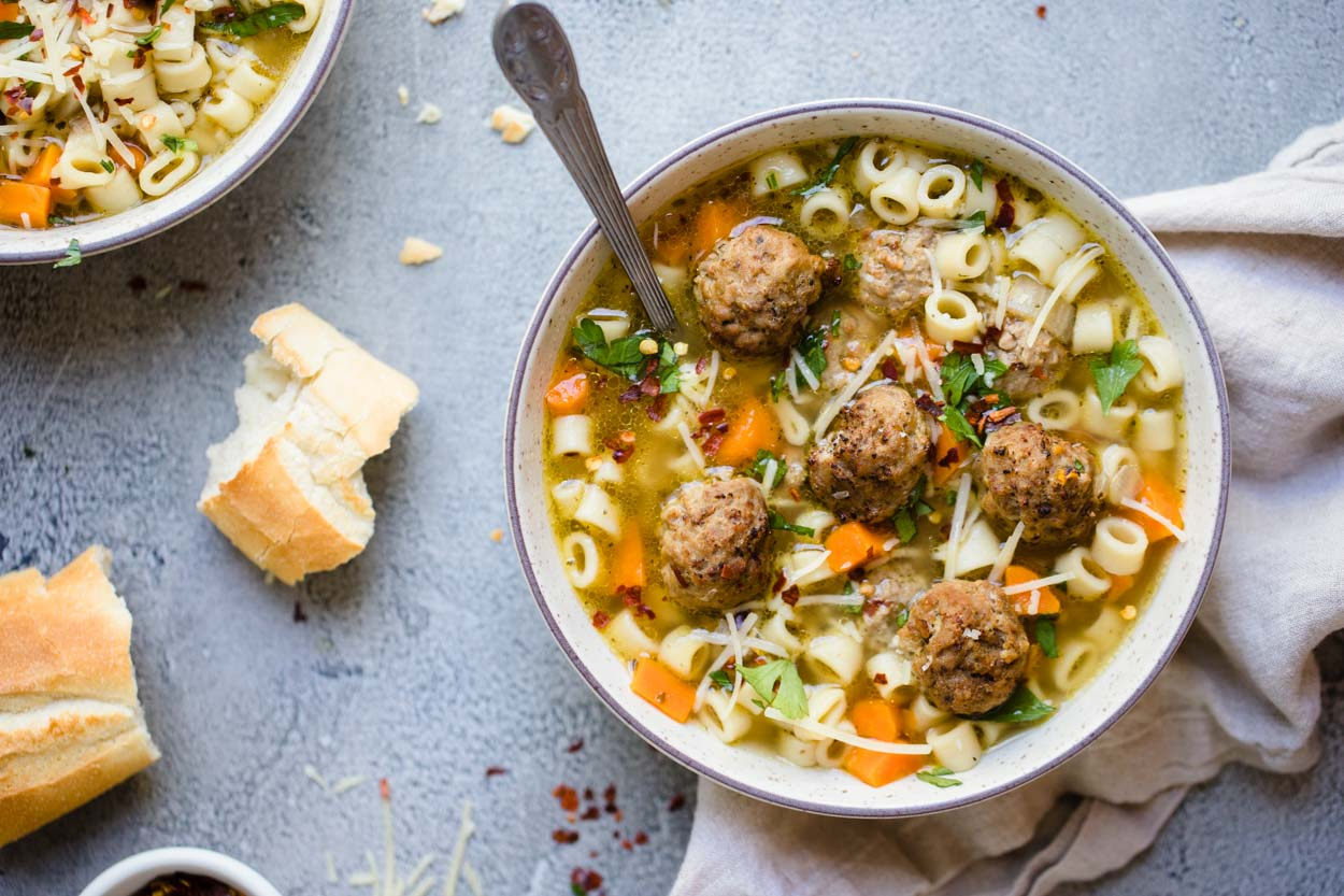 Bowl of meatball and pasta soup with crusty bread