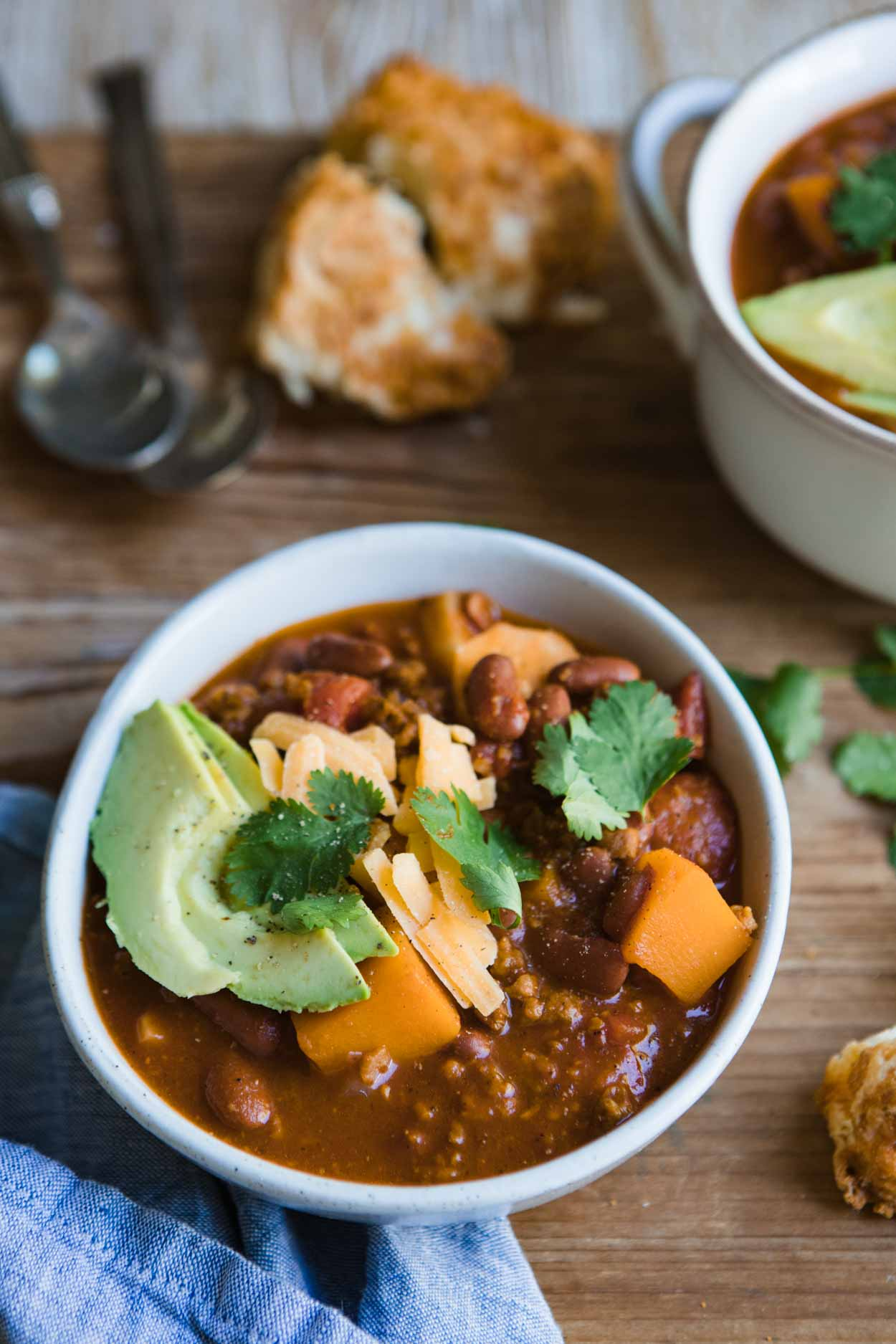 a bowl of vegetarian sweet potato chili with avocado, cheese and cilantro garnish