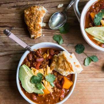 a bowl of sweet potato vegetarian chili with a spoon and cheddar biscuit