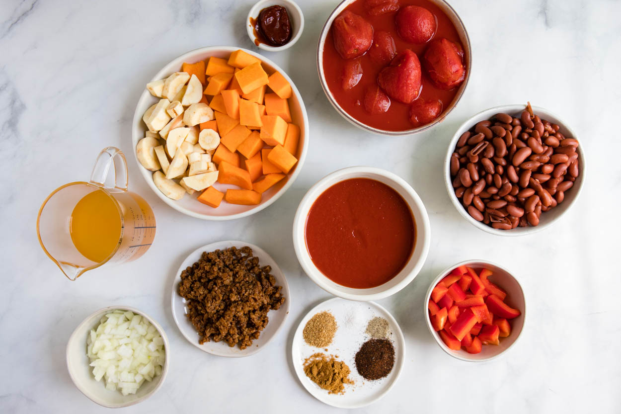 ingredients for sweet potato vegetarian chili in round bowls displayed on a white board