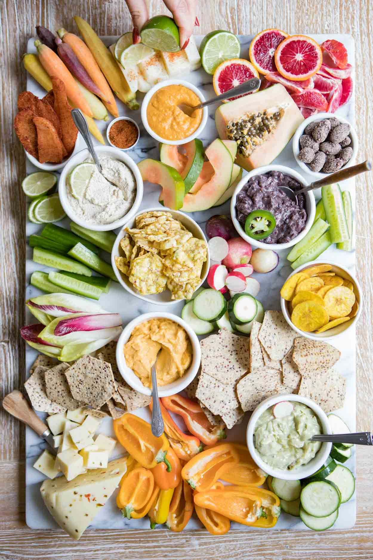 cucumbers, peppers, chips, dips and various other fruits and veggies on a marble slab for a crudite platter