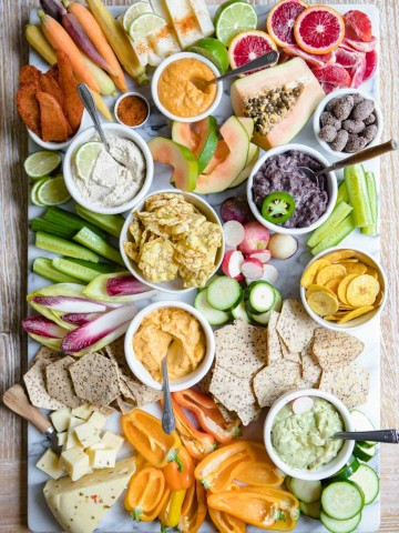 overhead shot of a fancy crudite platter with lots of fruits and veggies and snacks on a marble board