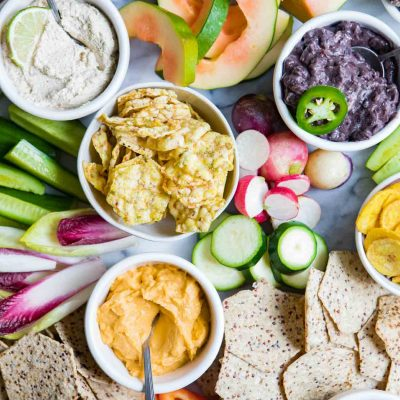 close up photo of fancy fruits and vegetables and crackers on a marble board for a crudite platter