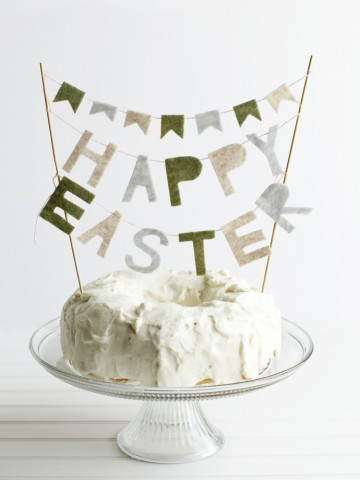 White frosted cake on a glass pedestal stand with a felt happy Easter banner
