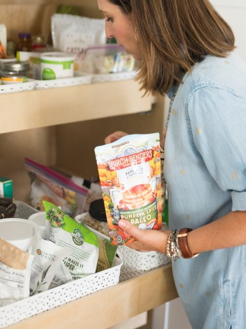 pantry cupboard filled with packaged foods and snacks and woman holding a package of pancake mix