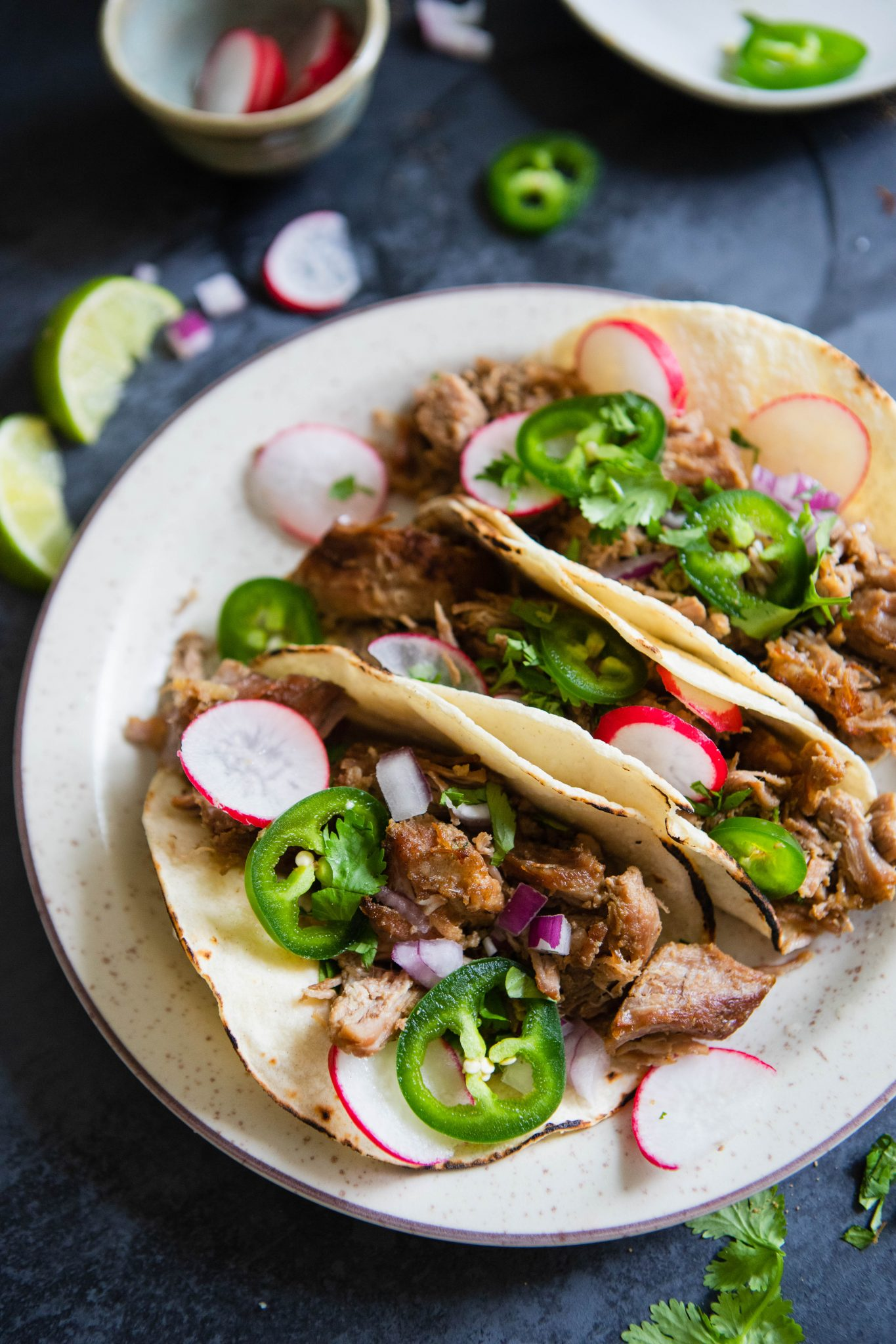 tacos stuffed with carnitas and topped with garnishes