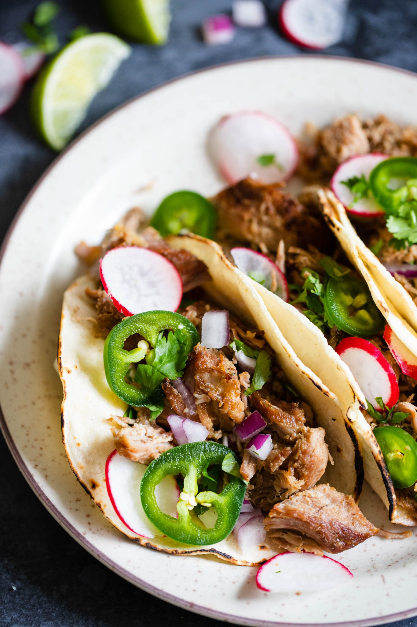 corn tortillas filled with Dutch oven carnitas and topped with radishes and jalapenos