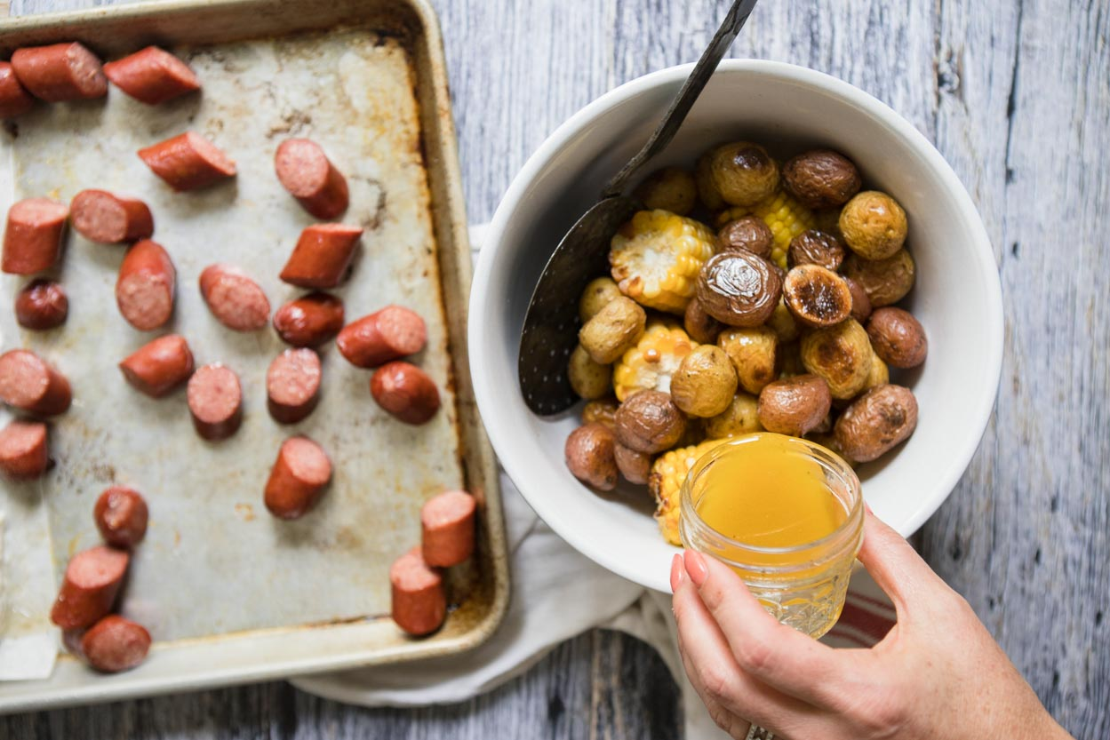 Butter sauce being poured over potatoes and corn next to a tray of sausage
