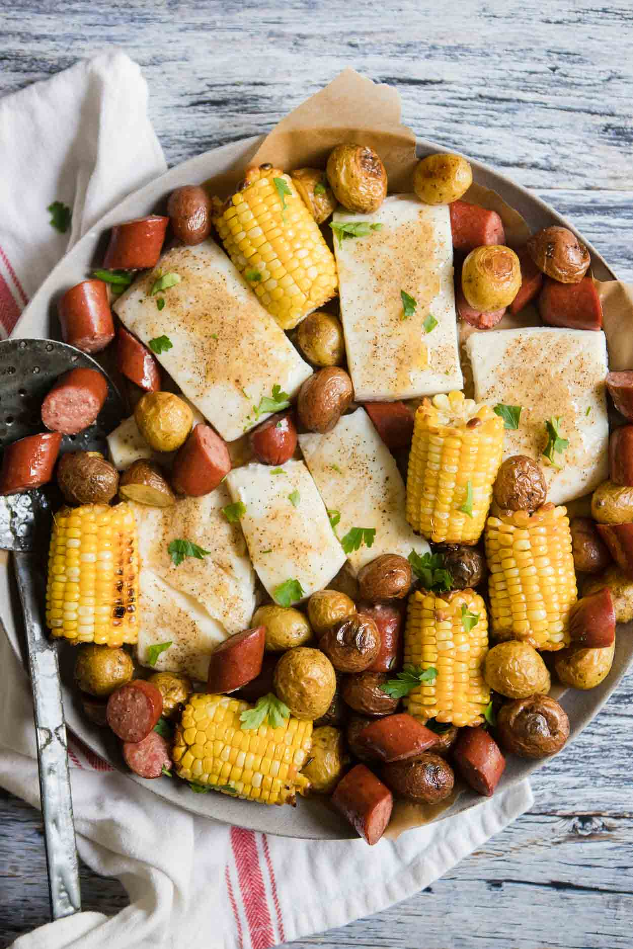 close up of a round platter filled with corn, sausage, halibut and potatoes