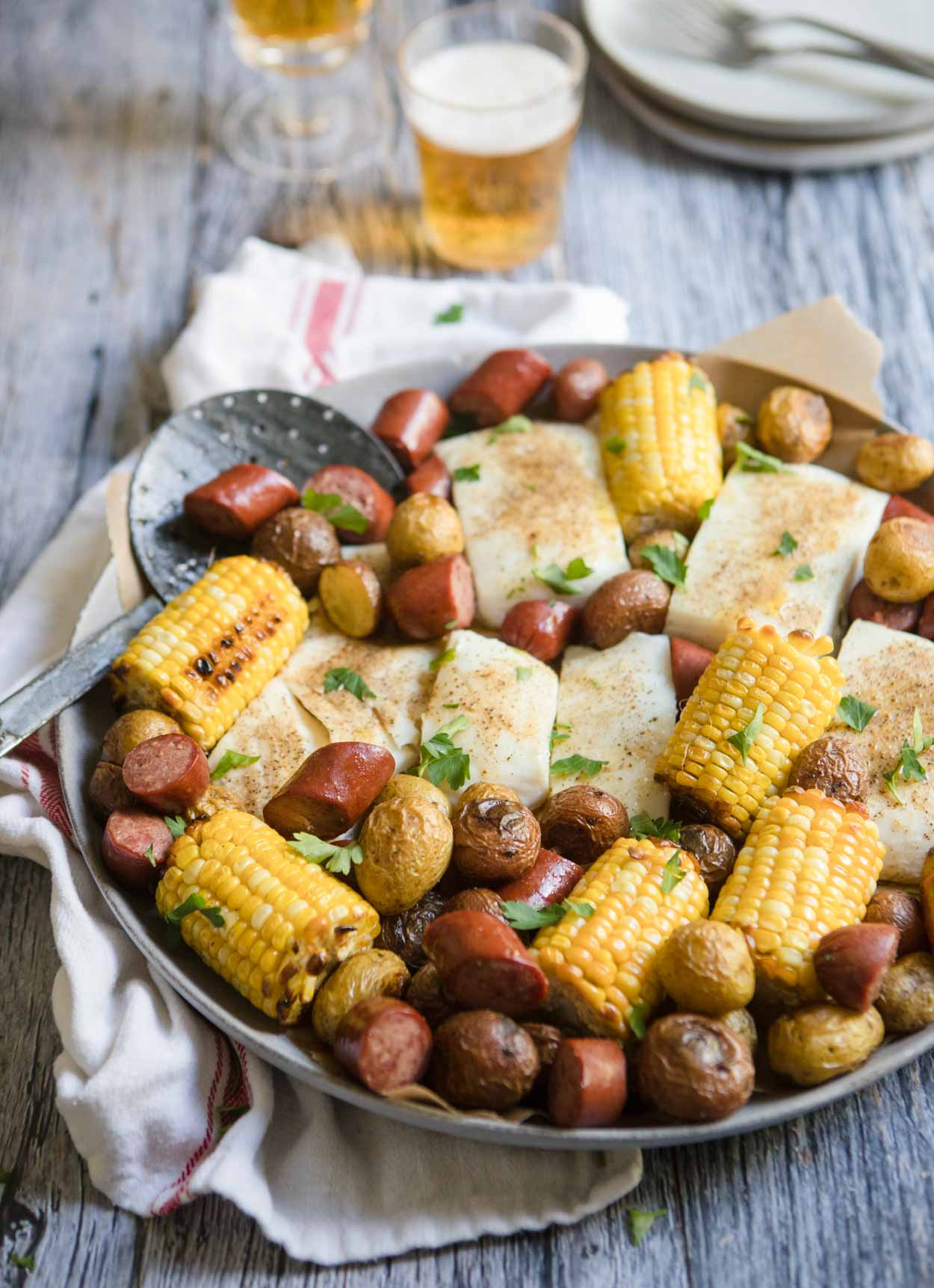 round platter with sausage, halibut, corn and potatoes set against a gray backdrop