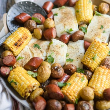 halibut, sausage, corn and potatoes on a round platter with seasoning on top